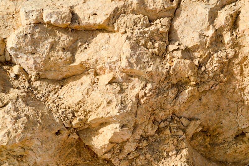 texture d'un mur de roche arénacée d'une vieille pierre putréfiée friable jaune de roche avec des tessons, des trous et des couch images libres de droits