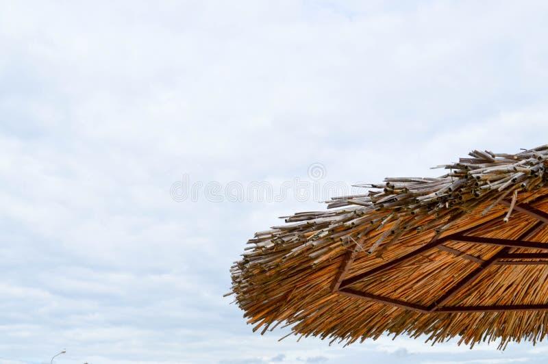 Texture d'un parapluie de soleil sec de plage de paille naturelle fait à partir de l'herbe sèche et des branches de foin sur la p photos stock