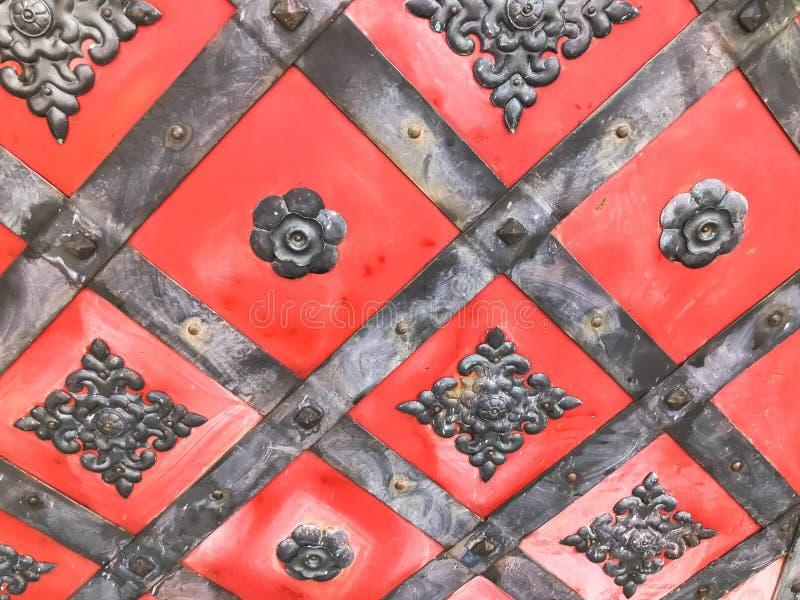 Texture d'une vieille porte vigoureuse antique rouge médiévale antique en métal de fer avec des rivets et des modèles de clous Le image stock
