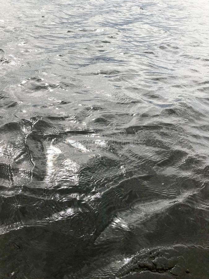 Texture of dark black cold water with waves of ripples rippling. The background.  royalty free stock image