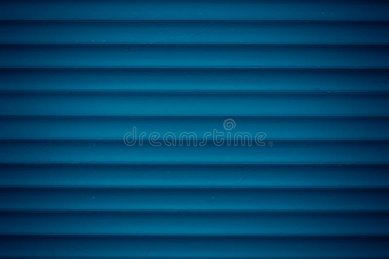 Texture of dark blue metal jalousie. Ribbed background with stripes, straight lines. Modern backdrop of striped fence. Texture of dark blue metal jalousie royalty free stock photos
