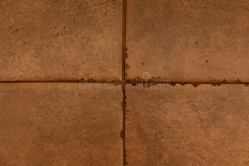 Texture of dark brown ceramic tiles. Texture of yellow brown ceramic tiles with joints and seam stock photo
