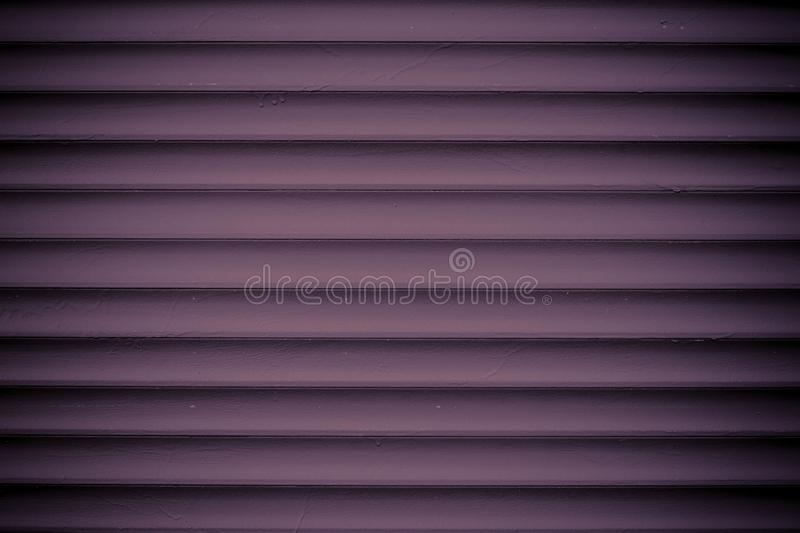 Texture of dark vinous metal jalousie. Ribbed red fence. Striped background. Modern backdrop. Burgundy slats. Abstract pattern of. Lines. Metallic surface royalty free stock images