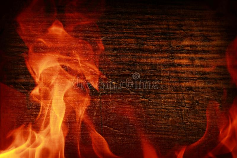 Texture of dark wood and frame out of the fire. Wood brown texture around the burning bright flame. Background of old panels. stock images