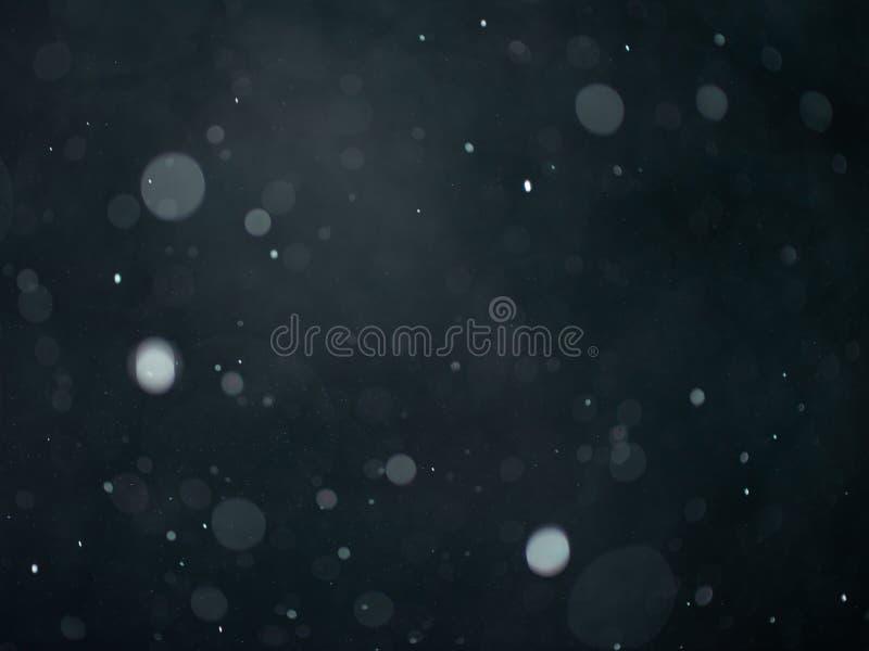 Texture de bokeh de neige ou de pluie sur le fond gris-foncé noir images stock