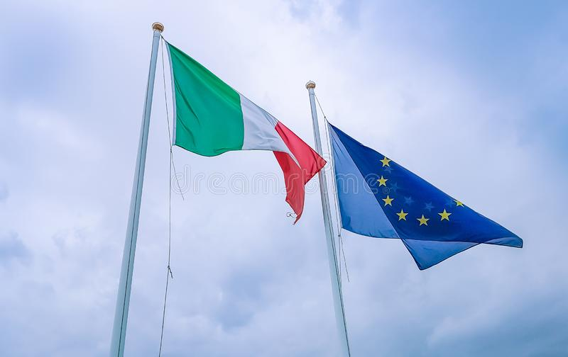 Texture de ondulation de tissu du drapeau de l'Italie et de l'union l'Europe sur le ciel bleu avec des nuages, concept photographie stock