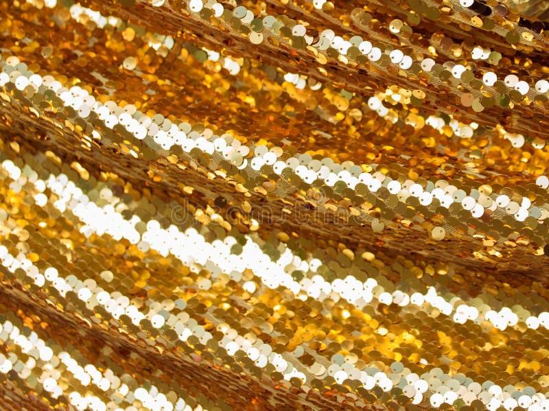 Texture de tissu avec des paillettes d'or abr?gez le fond images stock