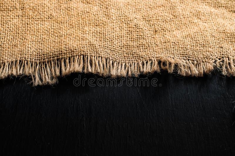 Texture de toile de jute de tissu de Brown sur la table en bois foncée images stock