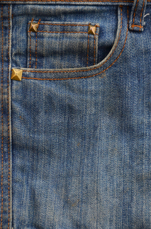 The texture of denim pocket. Texture fragment of denim in classic tones with bright seams of thin fabric and a large pocket. The background image on the royalty free stock image