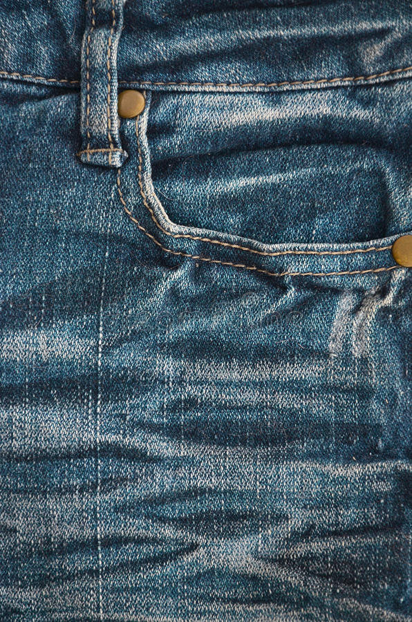 The texture of denim pocket. Texture fragment of denim in classic tones with bright seams of thin fabric and a large pocket. The background image on the stock image