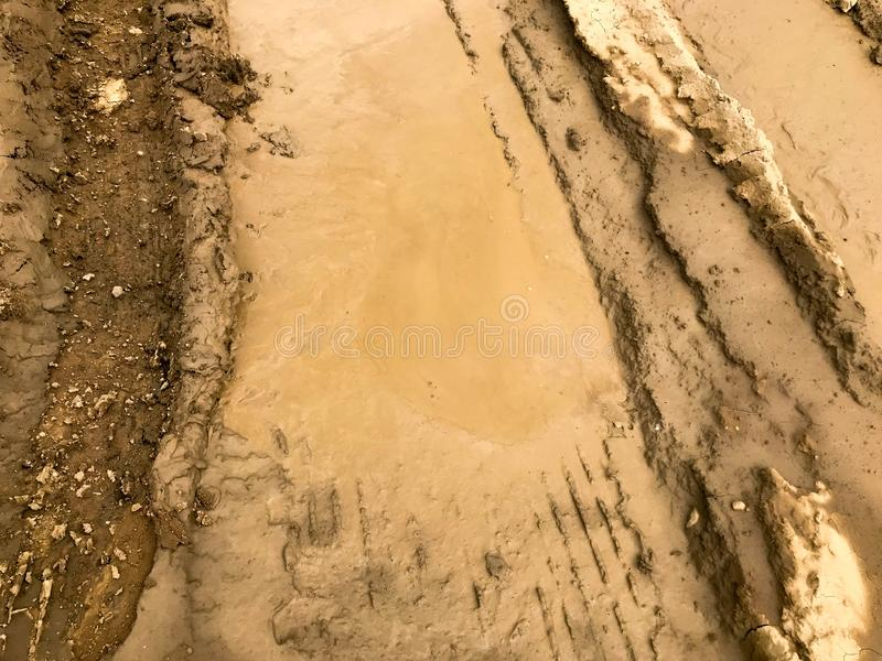 Texture of a dirty bad dirt road dirt road with puddles and clay drying mud with cracks and ruts. Off-road. The background.  stock images