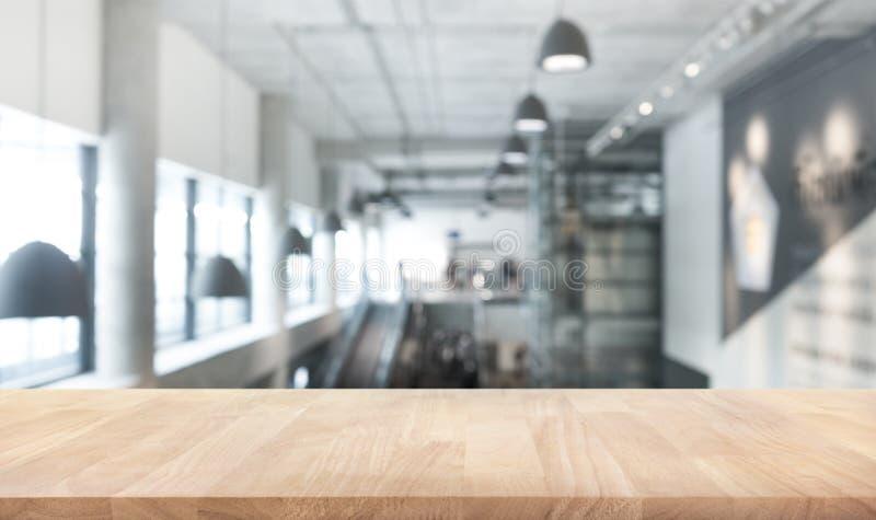 Texture en bois de dessus de table sur hall moderne/contemporain de tache floue de bâtiment photographie stock