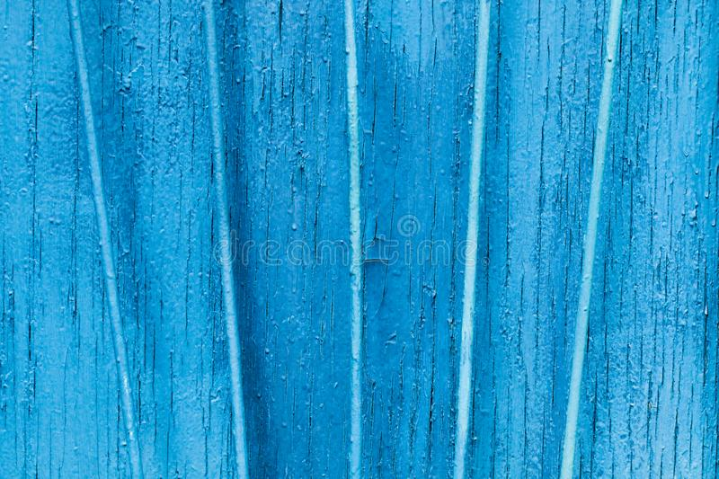 Texture exfoliating cracked blue paint. Vintage wooden background with vertical iron bars, with blue paint. stock image