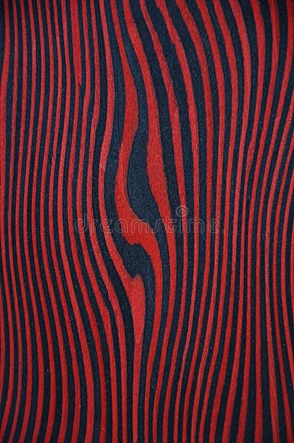 The texture of an exotic wood. Red background with black stripes. stock photography