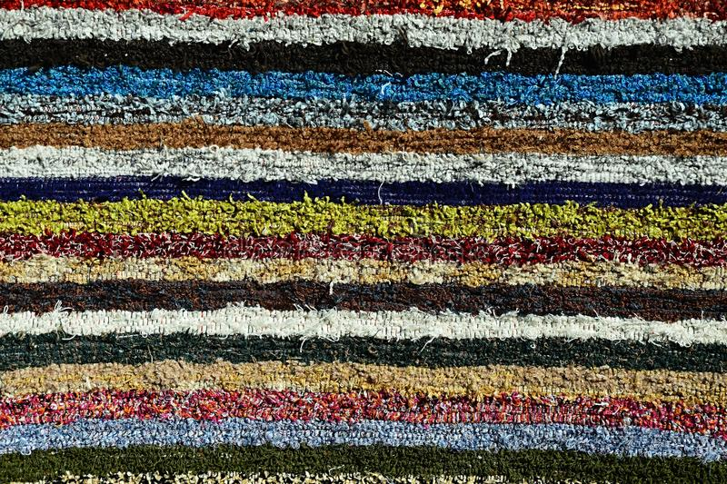 Texture of fluffy handmade carpet produced on hand-loom, pattern of various colorful vertical lines. Photograph taken on festival of traditional crafts in royalty free stock photos