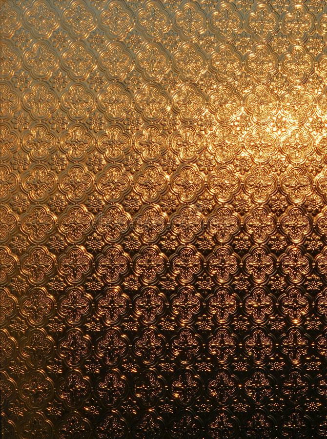Texture of a frosted glass window through which the rising sun shines has a golden-brown colour royalty free stock images