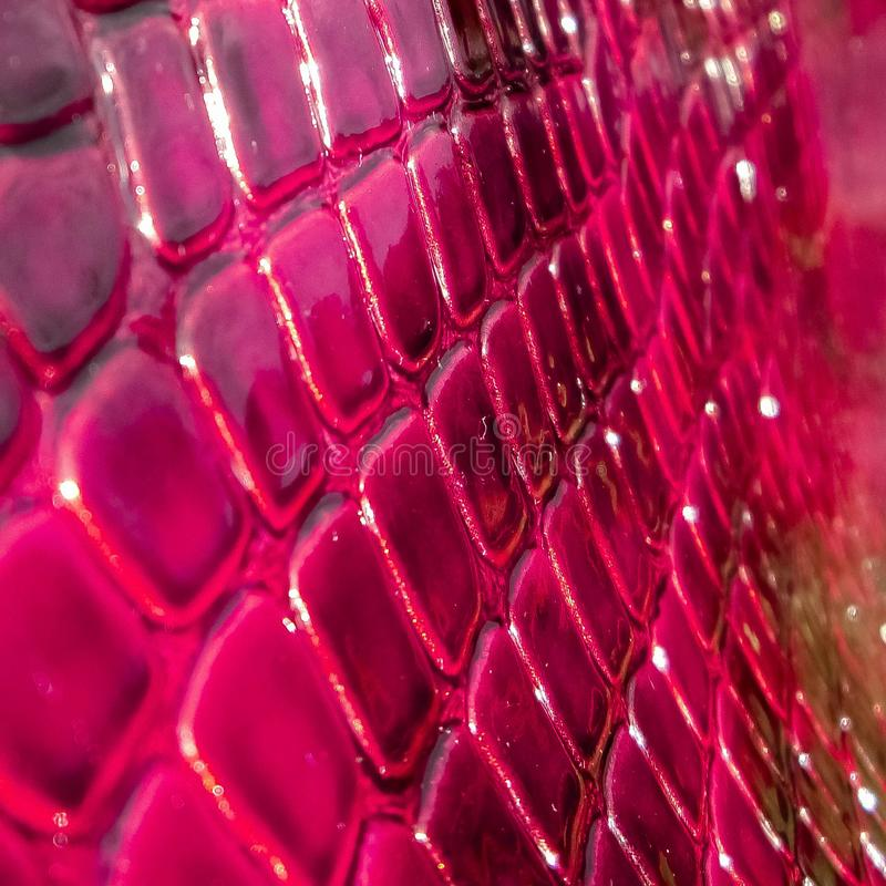 Texture of genuine patent leather close-up, embossed under the skin a red, pink reptile. royalty free stock photo