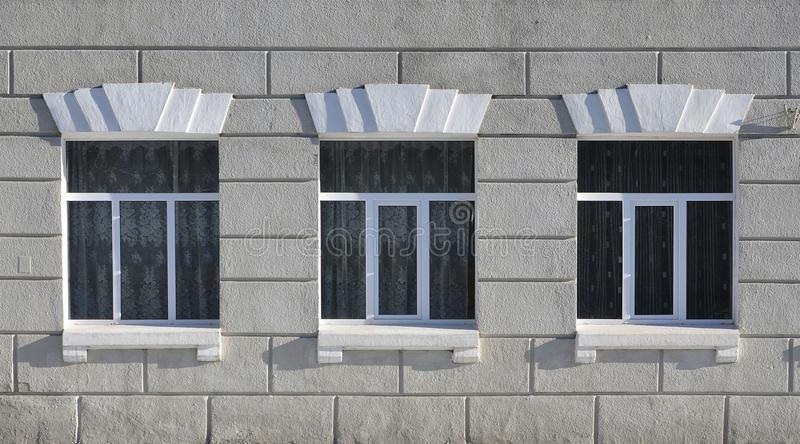 Texture of a glazed modern windows of a grey concrete building stock photography
