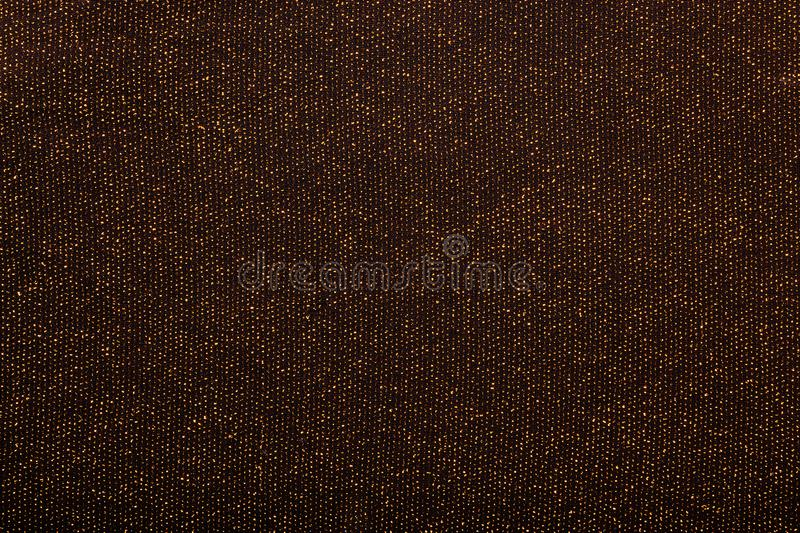 Texture of golden metallic threads in black fabric stock photography
