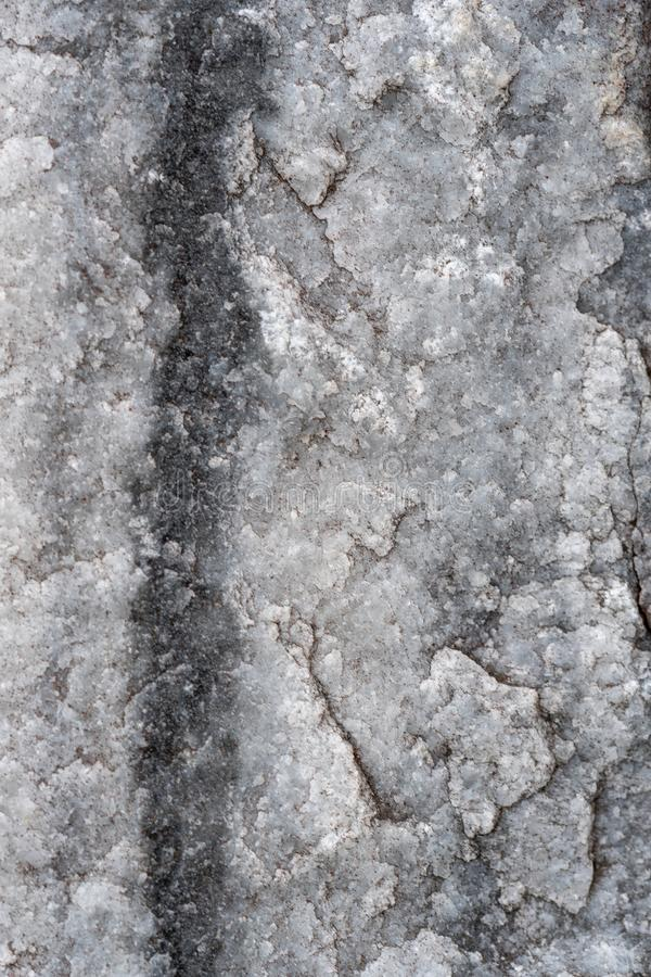 Gray surface of marble stone with striped streaks. Texture of gray natural marble. Durable and beautiful material for the construction of buildings and royalty free stock photography