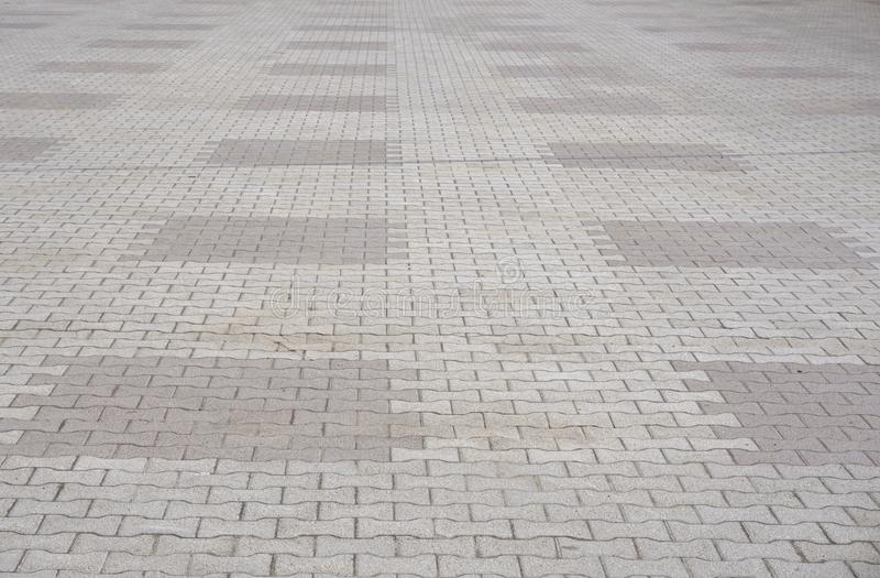 Texture of gray and yellow patterned paving tiles on the ground of street, perspective view. Cement brick squared stone floor back royalty free stock photos