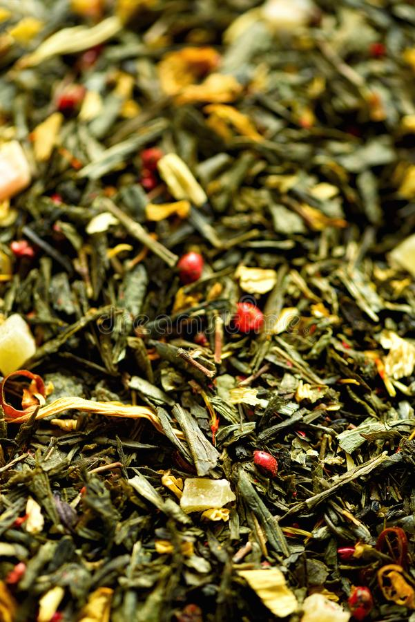 Texture of green tea with dried petals yellow flowers and red pepper. Food background. Organic healthy herbal leaves stock image