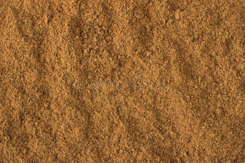 Ground nutmeg powder spice as a background, natural seasoning te. Texture of ground nutmeg powder close-up, spice or seasoning as background royalty free stock photography