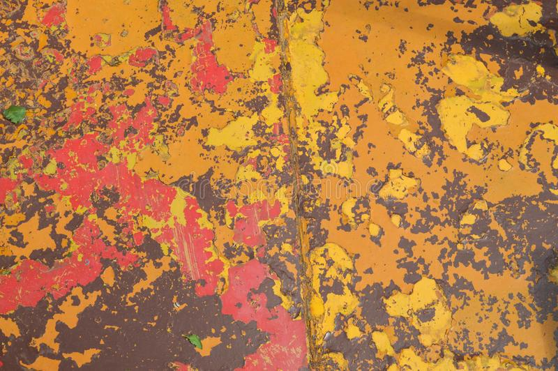 Texture of iron metal painted multicolored red yellow peeling paint of old battered scratched cracked ancient rusty metal sheet stock photos