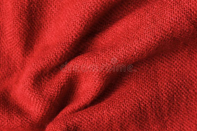 Texture of knitted read fabric. Light read thick winter fabric stock photo
