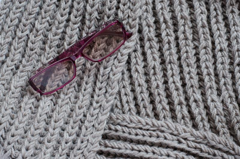 The texture of a knitted woolen fabric. Women`s sunglasses royalty free stock images