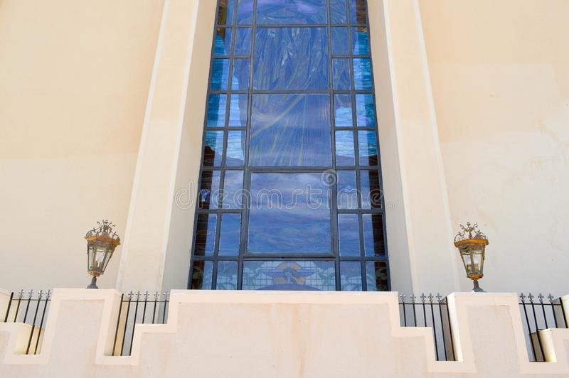 texture of a large huge glass blue window and a beige stone wall in the Egyptian Orthodox Christian church. The background. royalty free stock photo