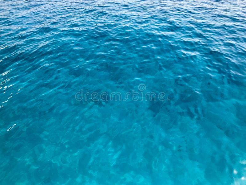 Texture light blue wet beautiful azure clean glowing warm transparent sea, ocean water, sea, ocean with small waves, light ripples stock photography