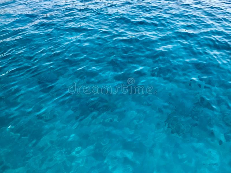 Texture light blue wet beautiful azure luminous warm transparent sea, ocean water, sea, ocean with small waves, light ripples. The royalty free stock image