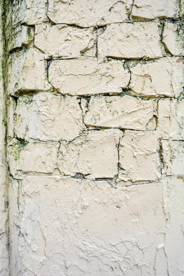Texture of light yellow paint stucco on brick wall. Imitation of old castle wall. Texture of old stucco and aged light yellow paint on brick wall background royalty free stock photography