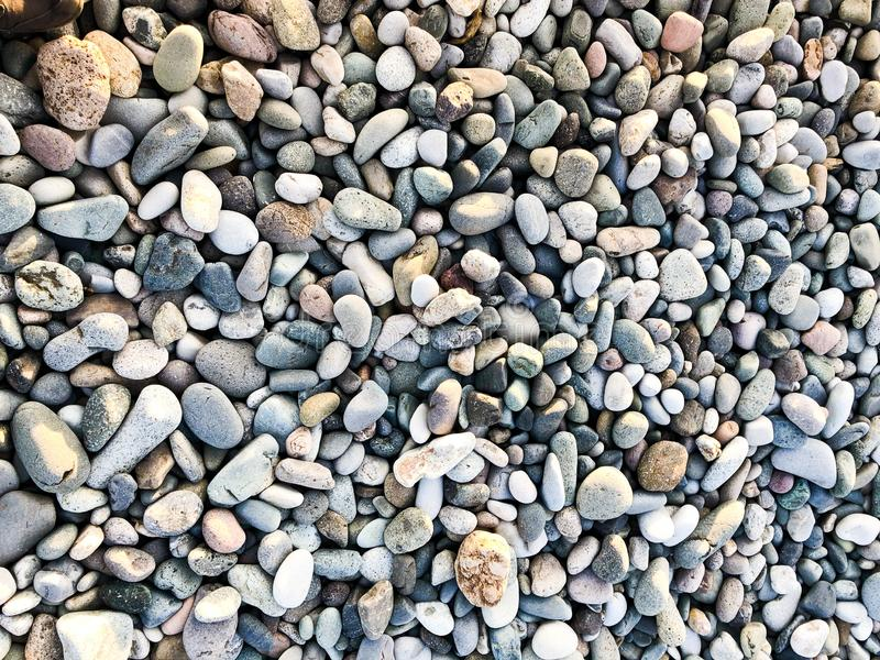 Texture of many multicolored beautiful round and oval smooth natural stones, pebbles. The background stock image