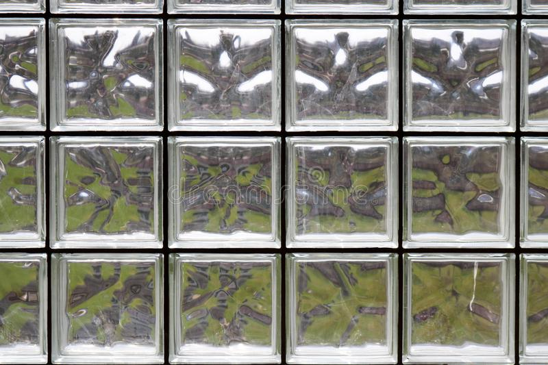 Texture of many shiny transparent beautiful square thick glass tiles with seams stock photo