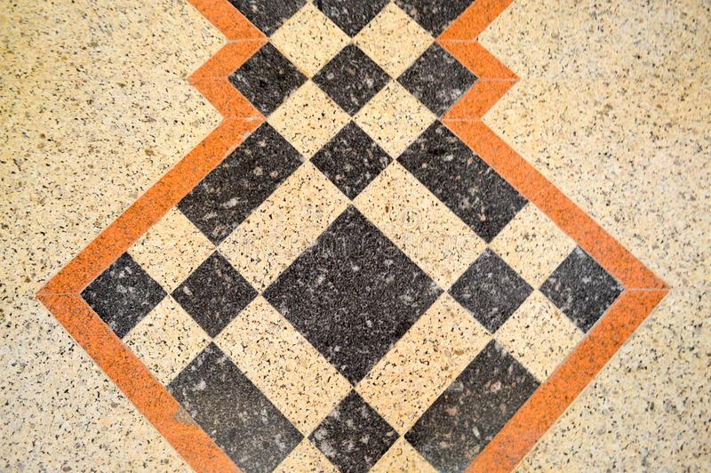Texture of the marble marble stone floor, tiles with brown, black and yellow squares, rhombuses and lines. The background. The texture of the marble marble royalty free stock photo