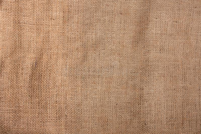 The texture of the Burlap. The texture of the material with a rough weaving of linen fibers of brown color. Burlap for decoration and design of web page and royalty free stock photo