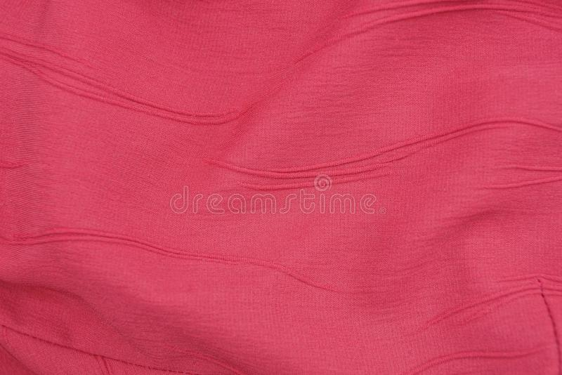 Texture of matter of red color from a piece of crumpled clothes. Red fabric background from a piece of crumpled clothes royalty free stock photo