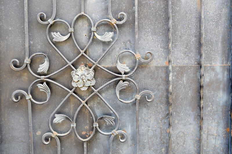The texture of a metal strong fence, a wall with a beautiful pattern of wrought iron flower from curved rods. The background stock images