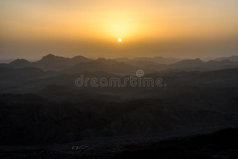 The texture of the mountains with the rising sun above them. Horizontal frame stock image