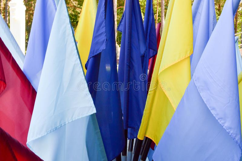 Texture of multi-colored festive red, blue, yellow flags made of fabric. The background royalty free stock photography