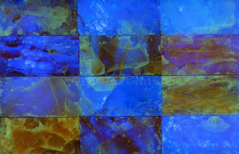 Texture of natural quartz stone with blue backlight. Blocks from natural stones with interior lighting stock image