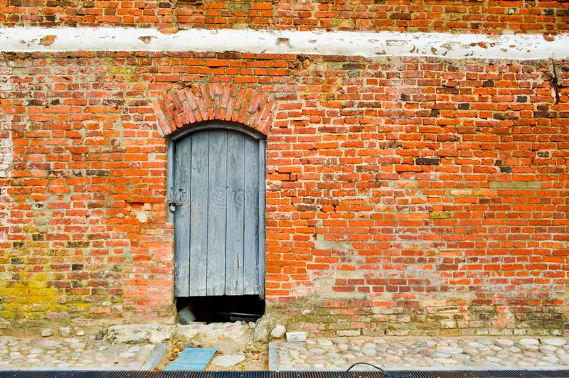 The texture of the old ancient medieval antique solid wooden thick door against the background of a stone wall of red brick royalty free stock photo