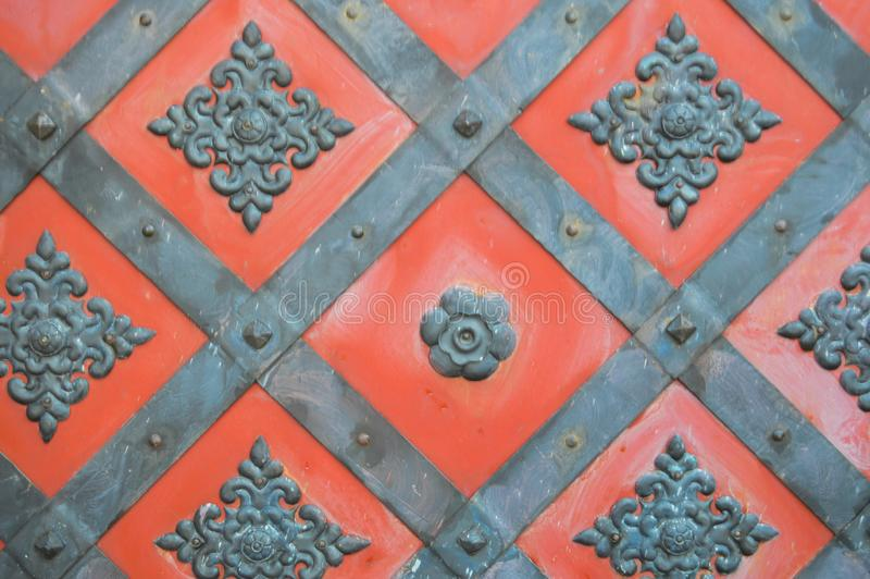 Texture of an old ancient medieval red antique sturdy iron metal door with rivets and nails patterns. The background royalty free stock image