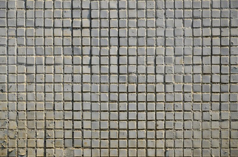 The texture of the old concrete wall, with a coating of shallow tiles of square shape, painted in gray. Background image of a wal. L of many square white tiles royalty free stock photo