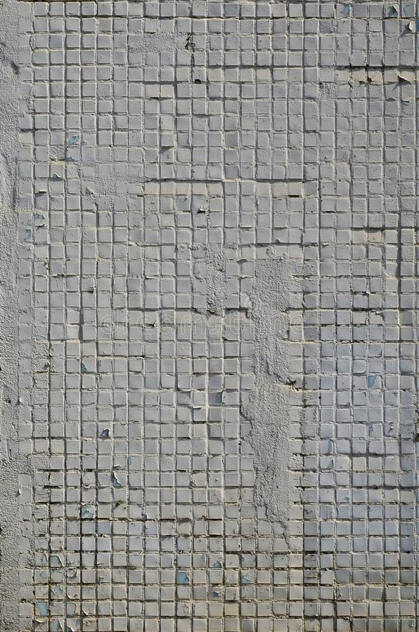 The texture of the old concrete wall, with a coating of shallow tiles of square shape, painted in gray. Background image of a wal. L of many square white tiles stock images