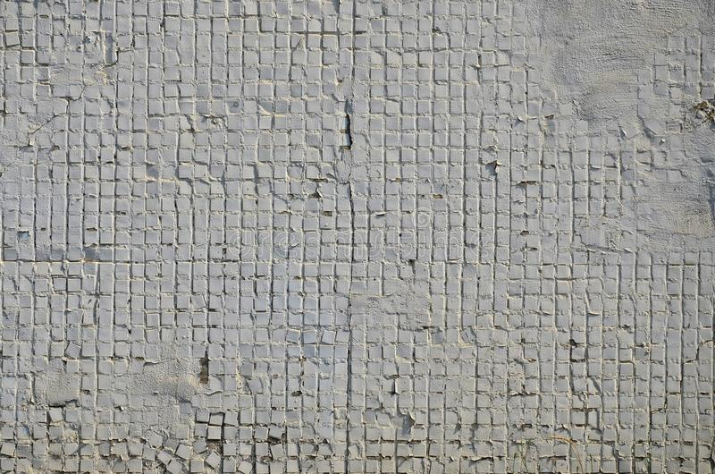 The texture of the old concrete wall, with a coating of shallow tiles of square shape, painted in gray. Background image of a wal. L of many square white tiles royalty free stock images