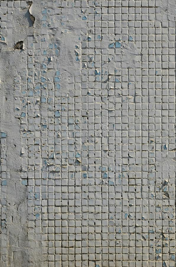 The texture of the old concrete wall, with a coating of shallow tiles of square shape, painted in gray. Background image of a wal. L of many square white tiles royalty free stock image