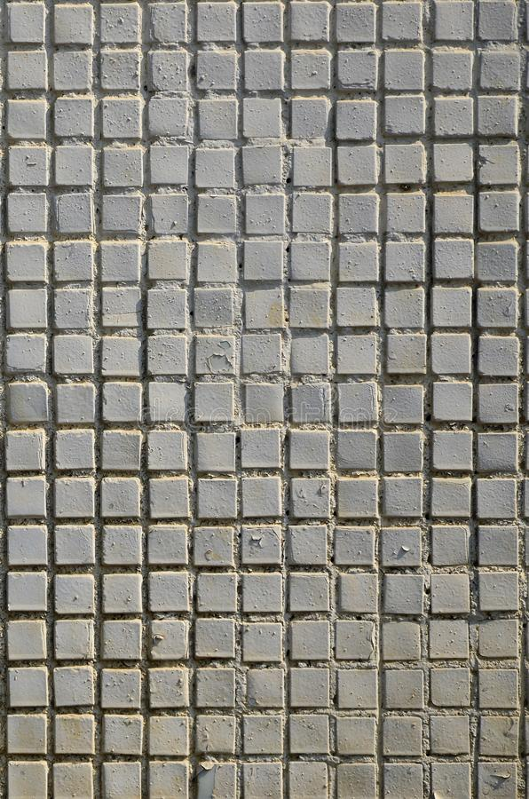 The texture of the old concrete wall, with a coating of shallow tiles of square shape, painted in gray. Background image of a wal. L of many square white tiles stock photos